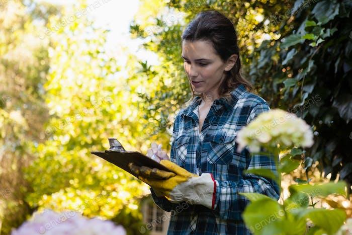 Female gardener writing on clipboard by flowers