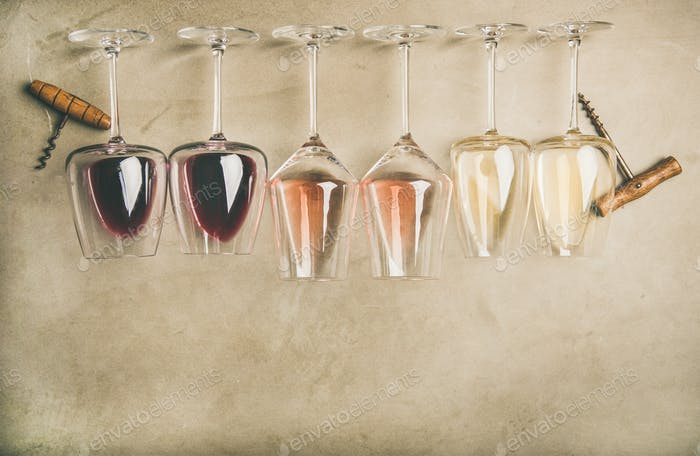 Different wines in glasses in row and corkscrews, top view