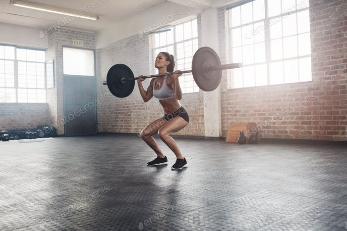 Fitness female athlete lifting weights in gym