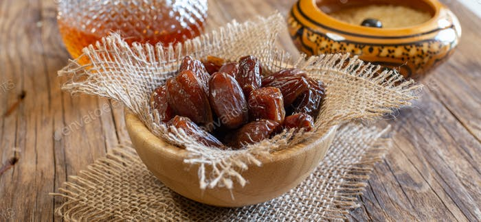 bowl of dried sweet dates on wooden table