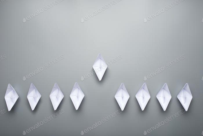 Neun aus Papier hergestellte Origami-Boote auf grauem Hintergrund