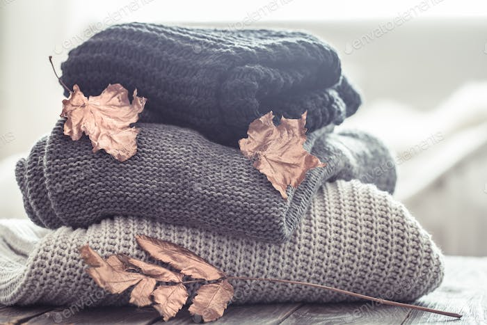 stack of cozy knitted sweaters in different colors.