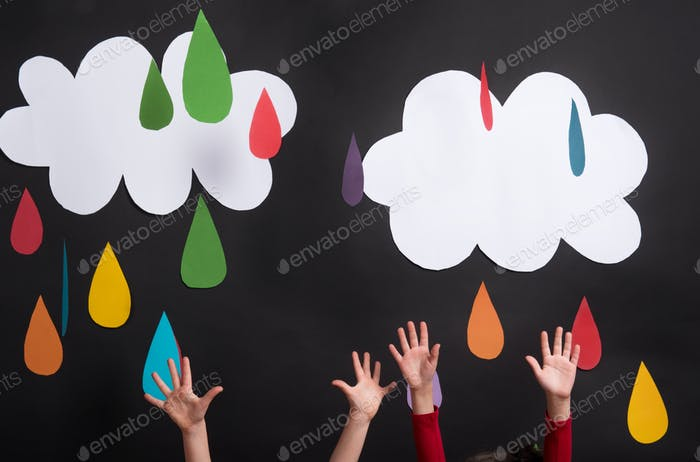 Hands of small girls in studio, reaching clouds and raindrops.