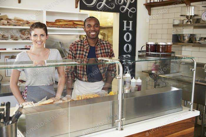 Mixed race couple waiting behind counter at a sandwich bar
