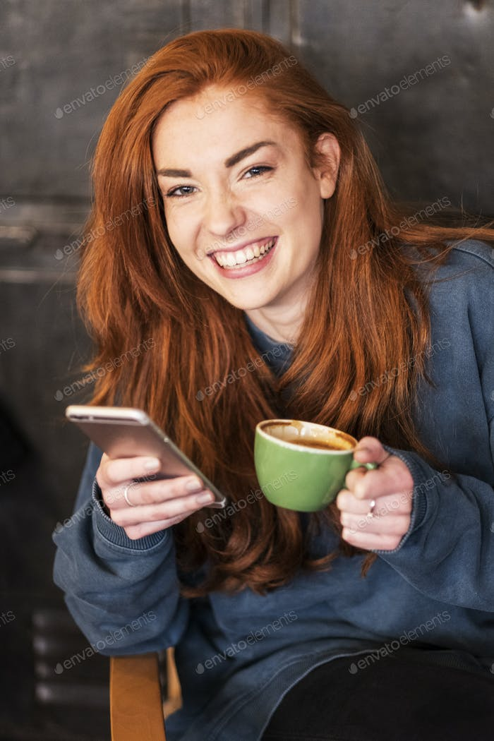 Smiling young woman holding mobile phone and coffee, working from home