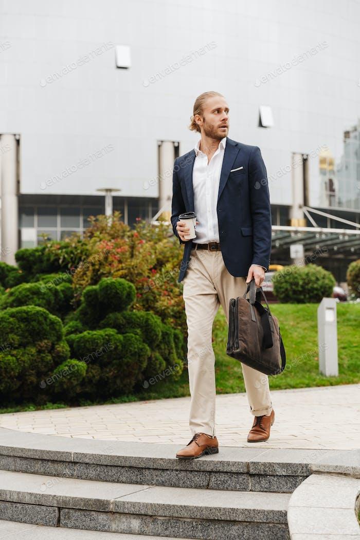 Bild des jungen Geschäftsmann hält Kaffeetasse zu Fuß auf der Stadtstraße