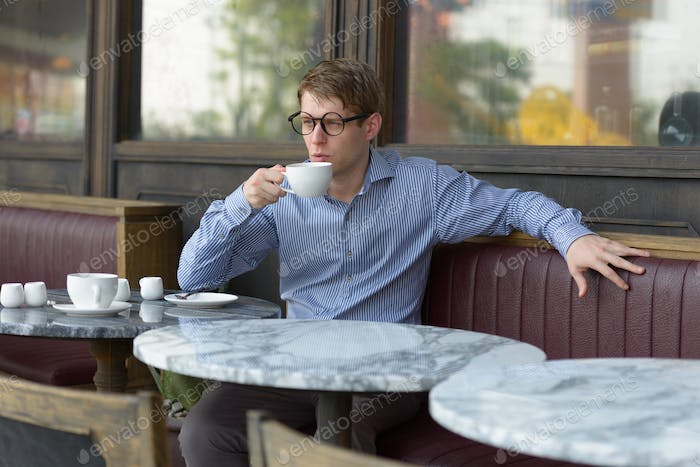 Young blond businessman drinking coffee at the coffee shop