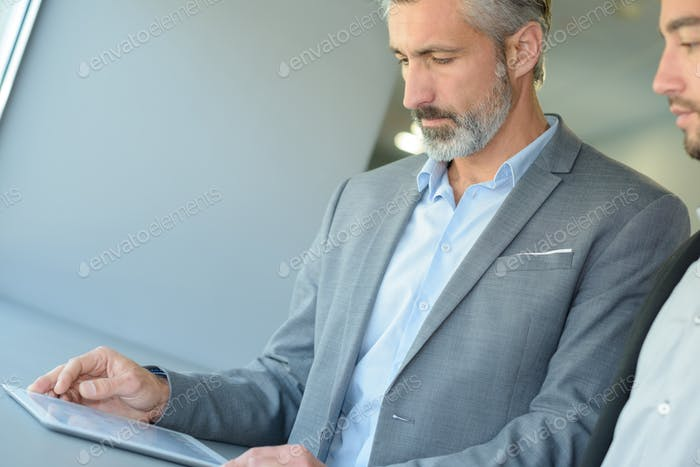 businessman showing his colleague info in a tablet