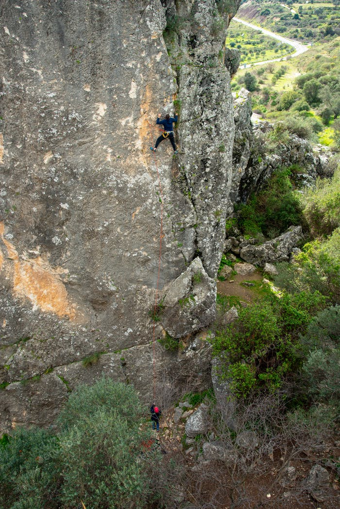 Unrecognized person climbing to the top of a Rock. Outdoor activities healthy lifestyle
