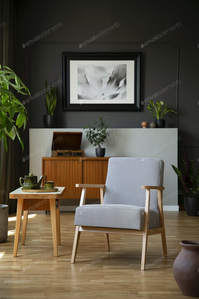 Patterned armchair next to wooden table in dark grey living room