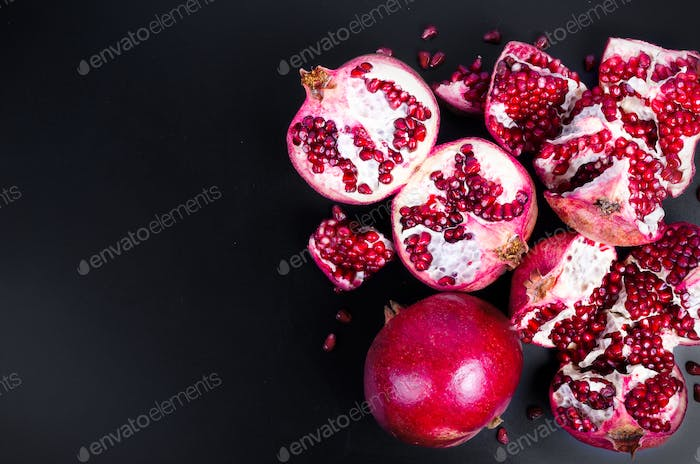 Broken pomegranate and grains on black background. Copy space