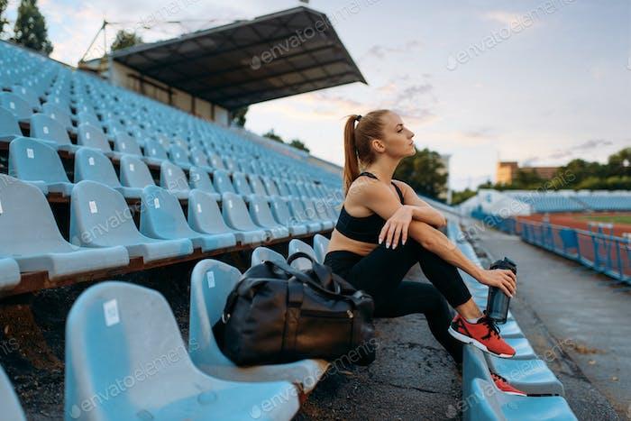 Female runner sitting on tribune and drinks water