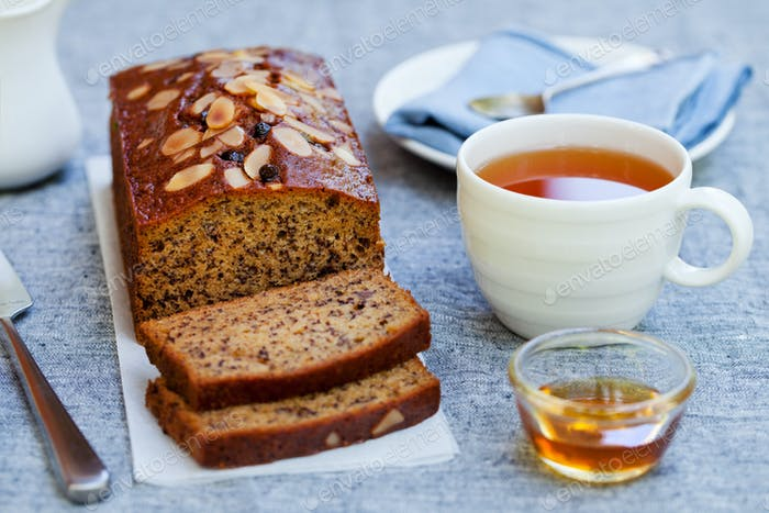 Banana, Carrot, Apple Cake, Loaf with Chocolate and Cup of Tea on Grey Background.