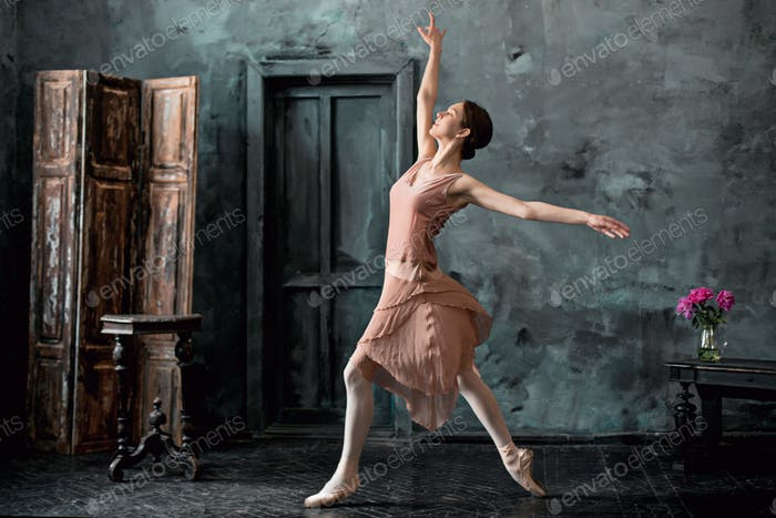 Young and incredibly beautiful ballerina is posing and dancing in a black studio