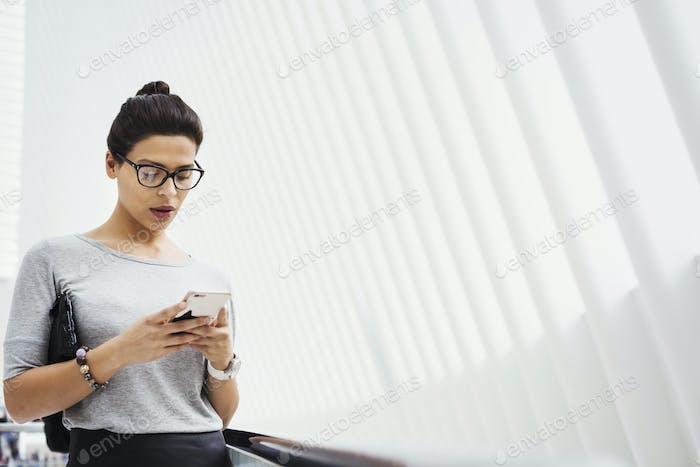 Eine Frau, die soziale Medien auf ihrem Handy überprüft, in einem hellen, luftigen Raum.