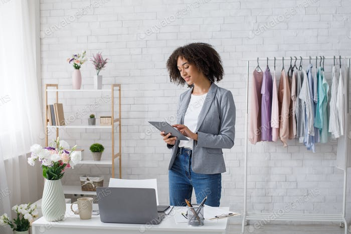 Fashion house, modern clothes. African american woman working in tablet