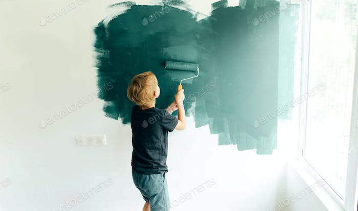 Little boy a preschooler paints in the room by the wall roller.