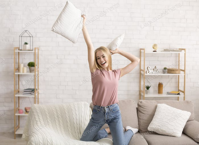 Happy young woman having fun alone at home