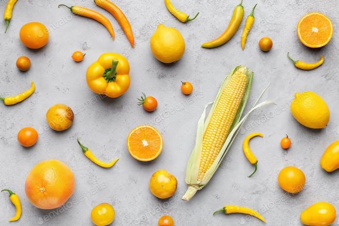 Sammlung von frischem gelbem Obst und Gemüse auf grauen Hintergrund
