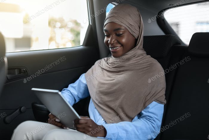 Modern Technologies For Business. Black Muslim Businesswoman Using Digital Tablet In Car