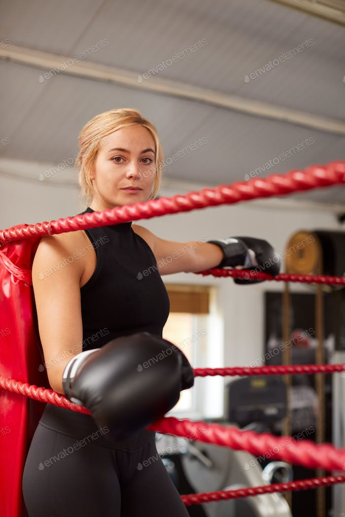 Portrait Of Female Boxer In Gym Wearing Boxing Gloves Standing In Boxing Ring