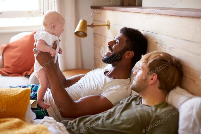 Loving Male Same Sex Couple Cuddling Baby Daughter In Bedroom At Home Together