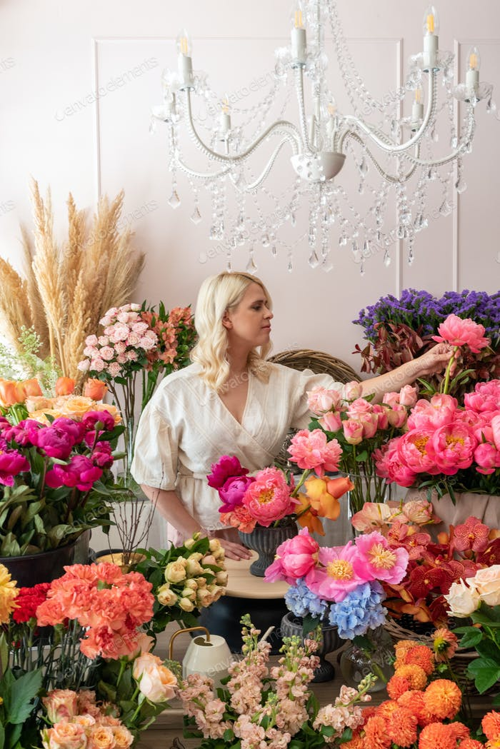 Beautiful blonde florist woman picks up flowers and creates wond