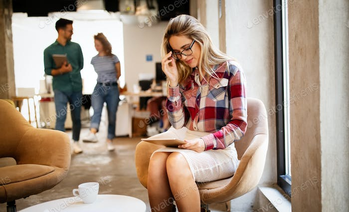 Business woman with a tablet, her co-workers discussing business matters in the background