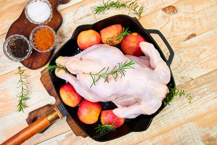 Whole raw chicken in skillet  or iron pan