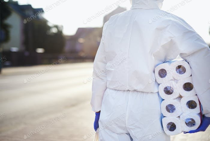 Person with toilet paper wearing a protective suit