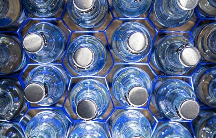 Clear Glass Water Bottles In Holders.