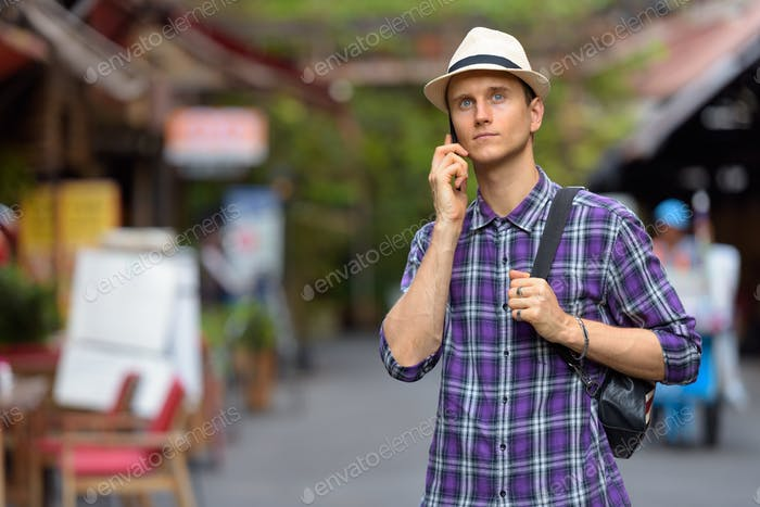 Portrait of young handsome tourist man using phone in the streets