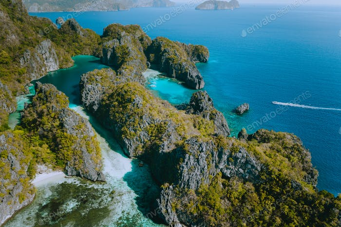 Aerial view of a unique blue lagoon surrounded by jagged limestone cliffs located on tropical