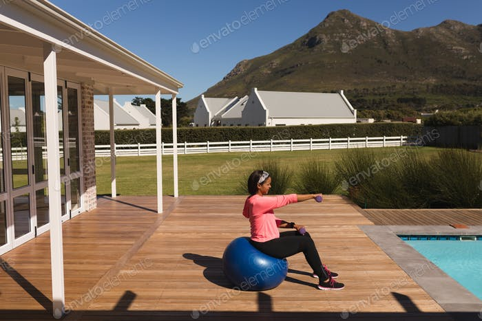 Woman exercising with dumbbells and exercise ball in the backyard of home