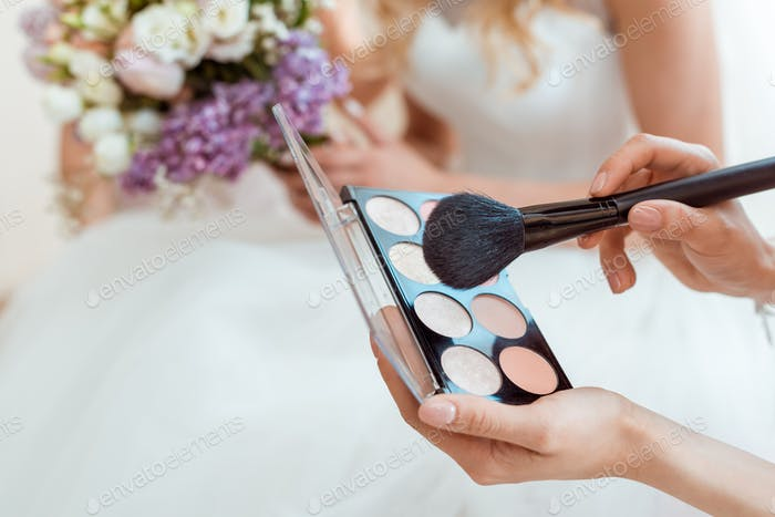 cropped shot of wedding makeup artist with powder