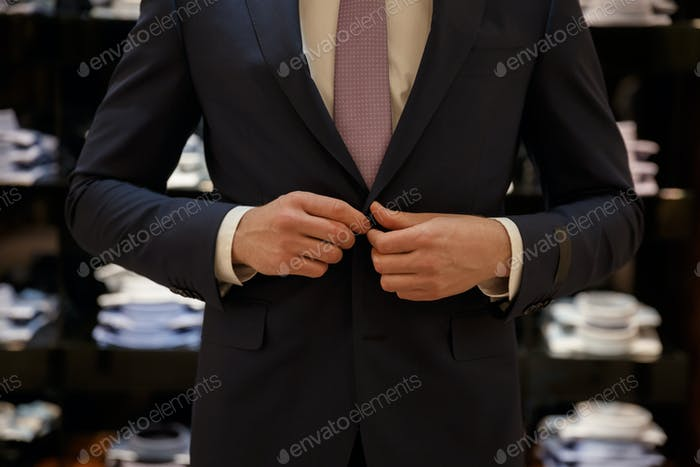 Cropped image of Man buttons up his jucket