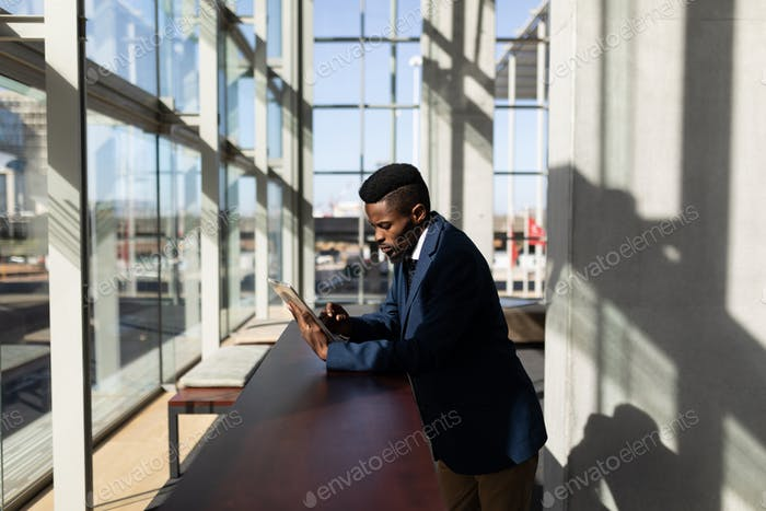 Businessman using digital tablet standing in modern office