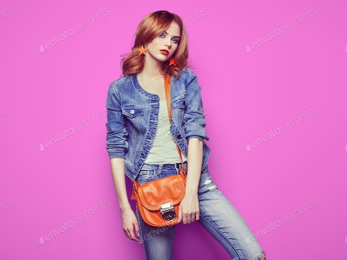 Fashion portrait of beautiful young woman with handbag