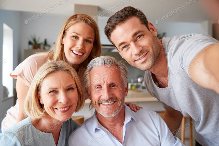Senior Parents With Adult Offspring Posing For Selfie At Home