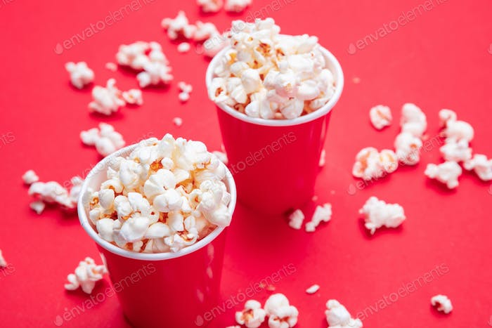 Pop corn in red paper cups on red color background