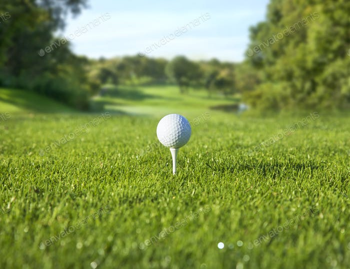 Low angle view of golf ball on tee in front of defocused fairway