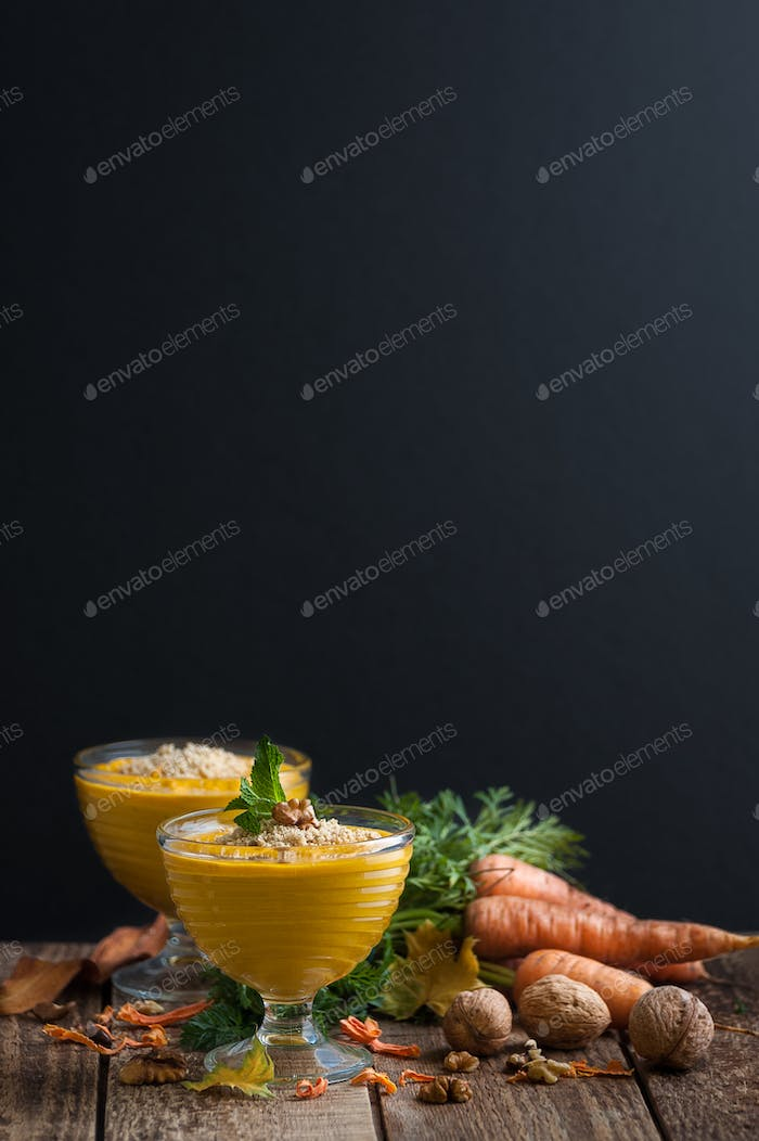 Carrot pudding with crushed nuts is served on a black background