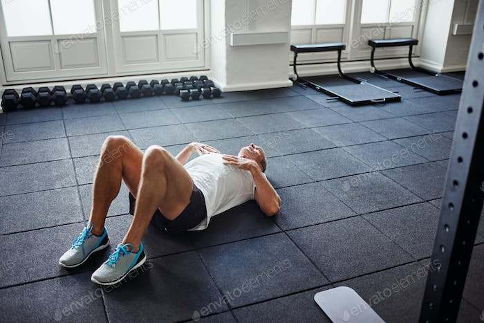 Tired man lying on a gym floor after working out
