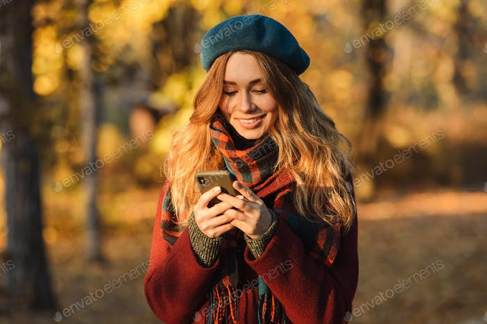 Happy young pretty woman walking outdoors in autumn spring park using mobile phone chatting.