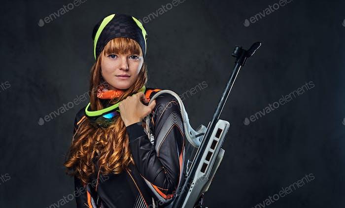 Redhead Biatlon female sportsmen holds competitive gun.