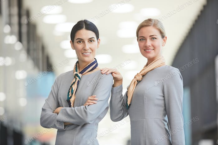 Two Smiling Flight Attendants in Airport