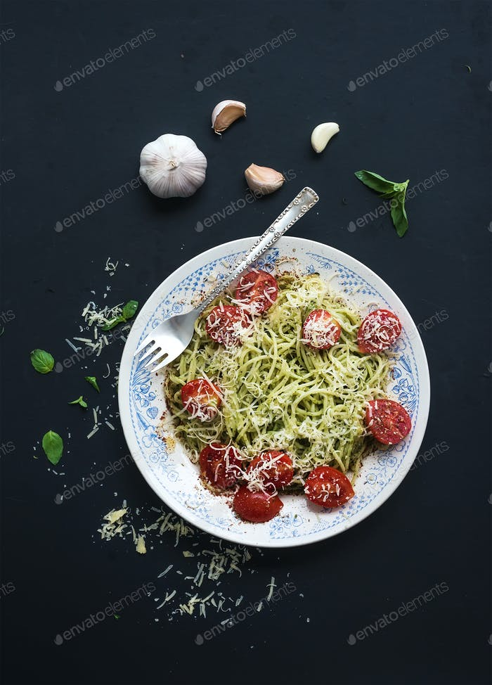 Pasta spaghetti with pesto sauce, basil, garlic, baked cherry-tomatoes