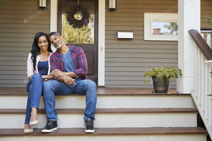 Couple Sitting On Steps Leading Up To Porch Of Home