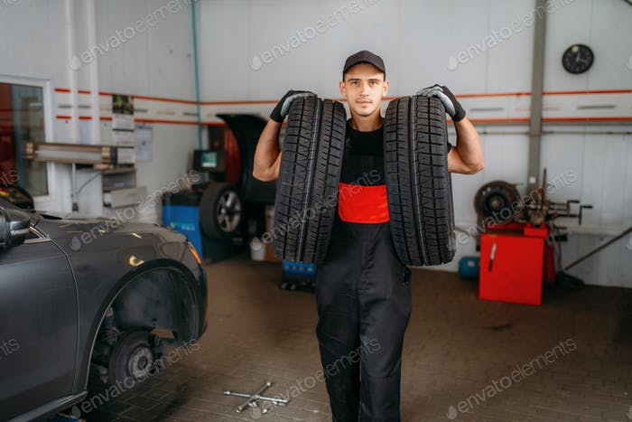 Auto repairman holds two tires, repairing service