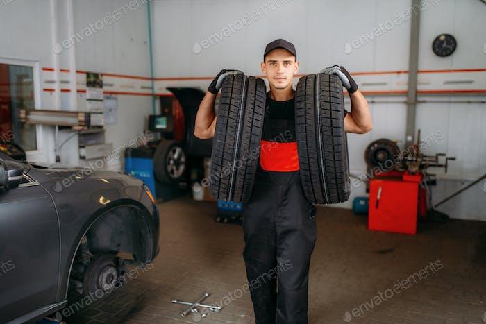 Auto Reparaturmann hält zwei Reifen, Reparaturservice